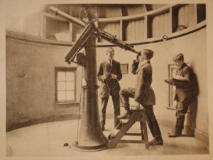 Photograph in Bootham School Observatory. One of the students shown is looking through a telescope.