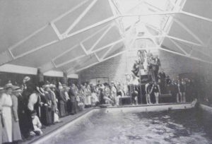Photograph of interior of Swimming Baths, 1914, with swimmers and spectators.